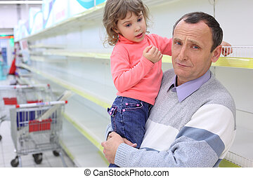 elderly man at empty shelves in  shop with child on hands