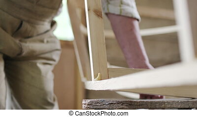 Elderly man carpenter builds a small boat with his hands out of wood in a small workshop