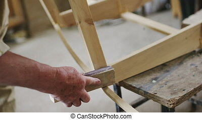 Elderly man carpenter builds a small boat with his hands out...