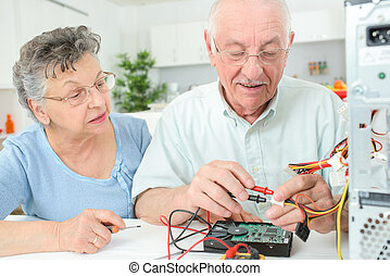 Elderly man checking computer with multimeter
