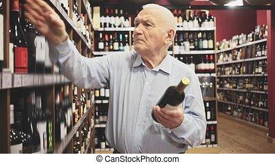 Attentive pensioner chooses red wine in a liquor store