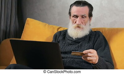 Elderly Man Does Online Shopping - Intelligent elderly man...