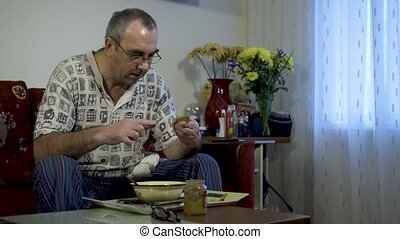 elderly man eating food at home in front of the TV