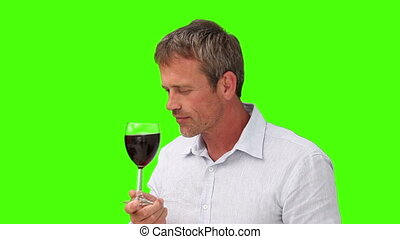 Elderly man enjoying glass of red wine