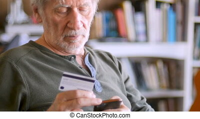Elderly man entering credit card numbers into his smart...