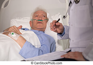 Elderly man examined by doctor - Elderly man in bed examined...