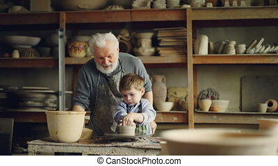 Elderly man experienced potter is teaching little boy how to work with clay on potter's wheel. Sharing experience, family tradition and modern pottery concept.