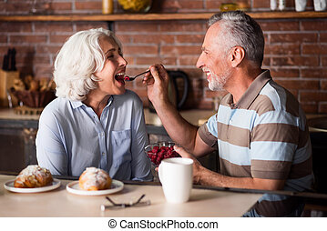 Elderly man feeding his lovely wife