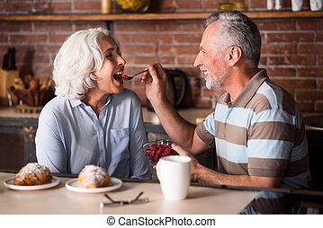 Elderly man feeding his lovely wife