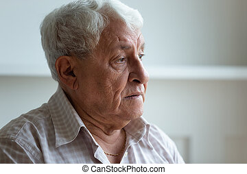 Elderly man feels sad and lonely looking away closeup face