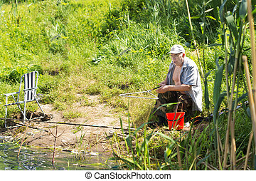 Elderly man fishing at the side of a lake