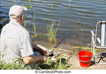 Elderly man fishing on a fresh water lake