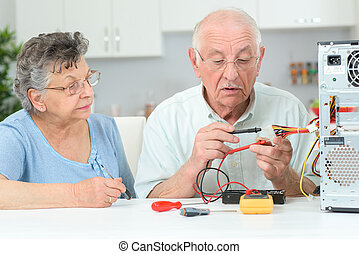 elderly man fixing a cpu