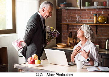 Elderly man giving flowers to his dear wife
