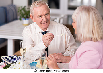 Elderly man giving his lady a cake - Want some. Attentive...