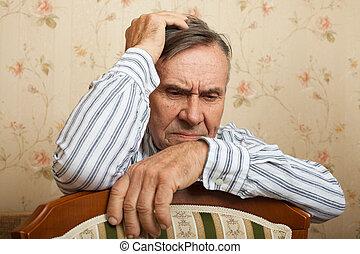 Elderly man grieves at home.