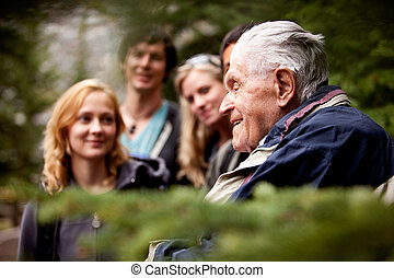 Elderly Man Group - An elderly man telling stories to a...