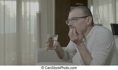 Elderly man having terrible sensitive toothache while he...