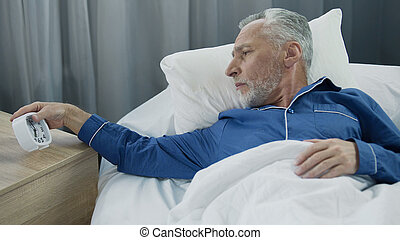 Elderly man hearing alarm clock, reluctant to wake up, lack of sleep and energy