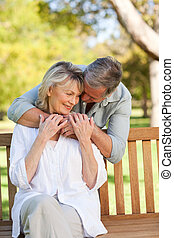 Elderly man hugging his wife who is on the bench