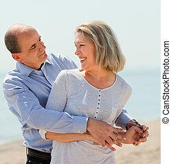 elderly man hugging woman