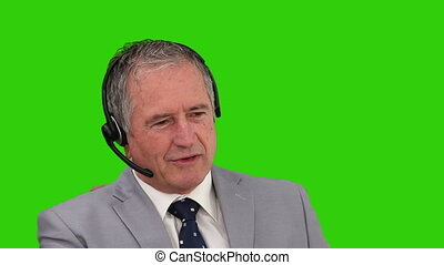 Elderly man in  a gray suit speaking over the headset