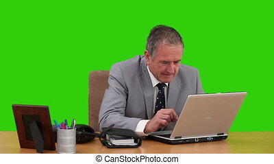 Elderly man in  a gray suit working on his laptop