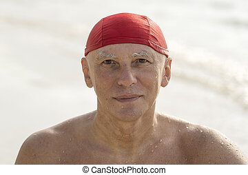 Elderly man in a red swimming hat on the beach near the sea water