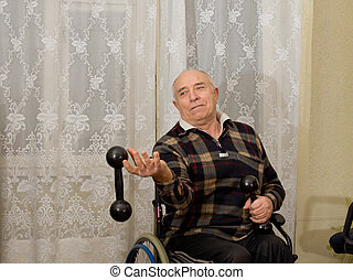 Elderly man in a wheelchair exercising with a pair of...
