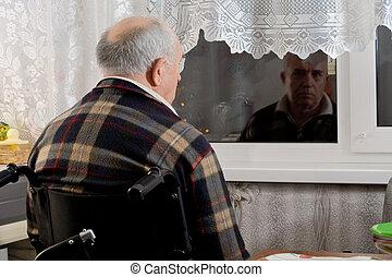 Elderly man in a wheelchair waiting at a window