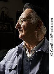 Elderly man in cap and eyeglasses sideview