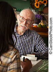 Elderly man in home with care provider or survey taker in...