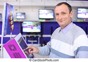 elderly man in shop at information screen