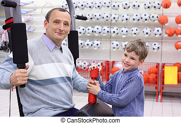 elderly man in shop on  sports exerciser and boy with barbell in hand