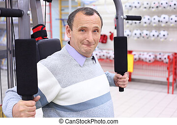 elderly man in shop on  sports exerciser