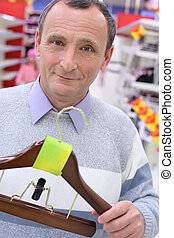 elderly man in shop with hanger for clothes in hands