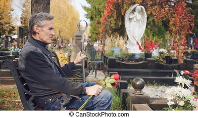 Elderly man in the cemetery talking alone