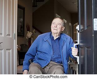 Elderly man in wheelchair at his front door, looking up -...