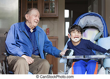 Elderly man in wheelchair laughing with disabled boy in kitchen