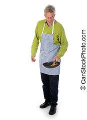 Elderly man is baking pancakes