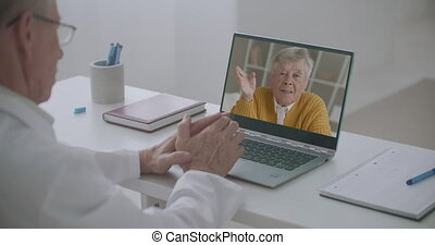 elderly man is calling to family doctor by video call, talking and consulting with him, doctor is looking at display of laptop