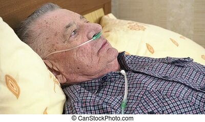 Elderly man is lying in bed at home with a medical oxygen catheter in his nose. Theme of a serious and incurable disease of lungs and respiratory system. Grandfather breathes in a special medical mask