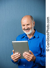 Elderly man laughing at information on his tablet