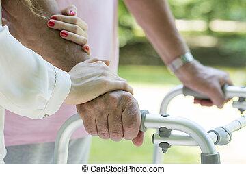 Elderly man leaned on the walking frame
