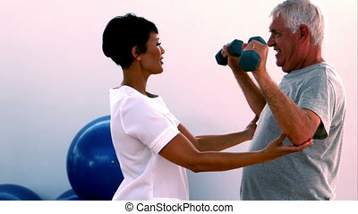 Elderly man lifting hand weights with physiotherapist -...