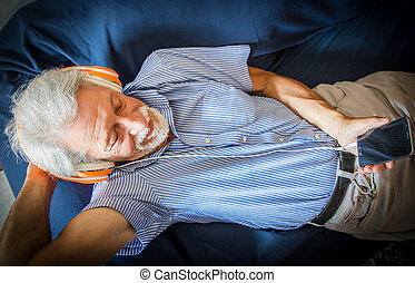 elderly man listen music with headphone on the couch