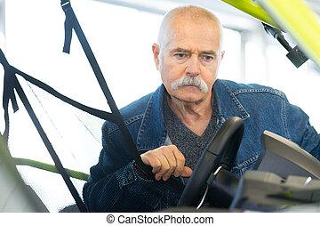 elderly man looking at new car in showroom