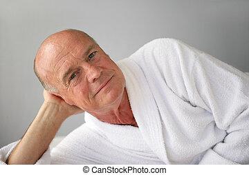 Elderly man lying in his bathrobe