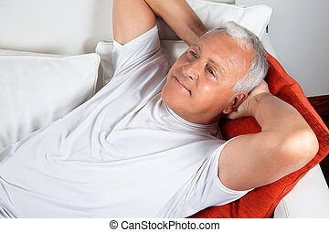 Elderly Man Lying in Sofa - Senior man relaxing on sofa with...