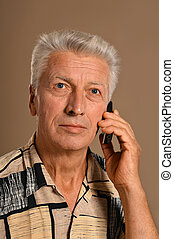 Elderly man makes call over brown background